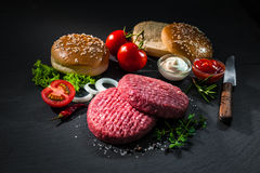 Raw beef patties with other ingredients for hamburgers Royalty Free Stock Image