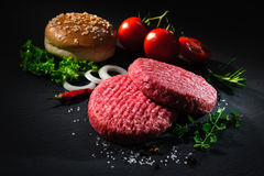 Raw beef patties with other ingredients for hamburgers Stock Images