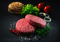Raw beef patties with other ingredients for hamburgers Royalty Free Stock Photos