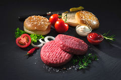 Raw beef patties with other ingredients for hamburgers Stock Photography