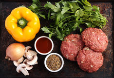 Raw beef patties. With vegetables, barbecue sauce and spices Royalty Free Stock Photo