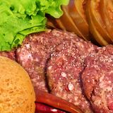 Raw beef patties with vegetables Royalty Free Stock Images
