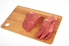 Raw beef piece and slices on wooden cutting board isolated on white background.  Stock Photo