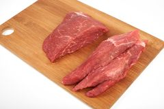 Raw beef piece and slices on wooden cutting board isolated on white background.  Royalty Free Stock Photos