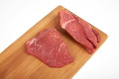 Raw beef piece and slices on wooden cutting board isolated on white background.  Stock Photography