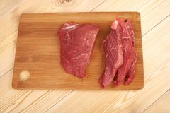 Raw beef piece and slices on wooden cutting board.  Stock Images