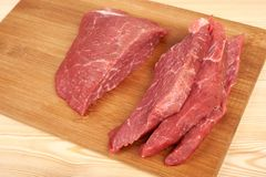Raw beef piece and slices on wooden cutting board.  Stock Photography