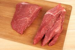 Raw beef piece and slices on wooden cutting board.  Stock Photo