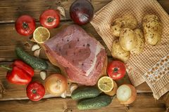 Raw beef with potatoes and vegetables on wooden boards. Big piece of fresh raw beef with potatoes and vegetables on the wooden table Stock Photo