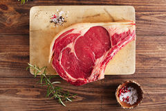 Raw beef Rib bone  steak   on wooden board and table Royalty Free Stock Photos