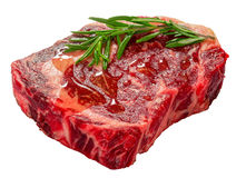 Raw beef rib eye fresh meat steak isolated on white. Background with rosemary and  poured with olive oil, close-up, view from above Royalty Free Stock Image