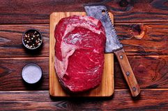 Raw beef rib eye steak on a bamboo cutting board on wooden background. Stock Photos