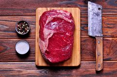 Raw beef rib eye steak on a bamboo cutting board on wooden background. Royalty Free Stock Image