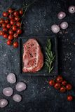 Raw beef rib eye steak with tomatoes, onion and rosemary on black background top view. stock image