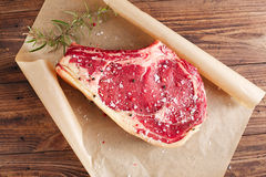 Raw beef Rib steak with bone on wooden board and table stock photos