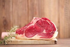 Raw beef Rib steak with bone on wooden board and table Royalty Free Stock Image
