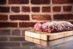 Raw beef ribe-eye steak with salt and pepper on butcher board stock photo