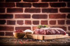 Raw beef ribe-eye steak with salt pepper and herbs on wooden butcher board stock photography