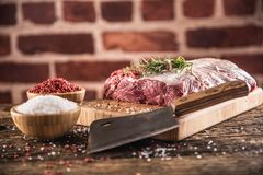 Raw beef ribe-eye steak with salt pepper and herbs on wooden butcher board royalty free stock photo