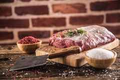 Raw beef ribe-eye steak with salt pepper and herbs on wooden butcher board royalty free stock image
