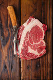 Raw beef Ribeye steak on wooden table. With vintage carving fork royalty free stock photos
