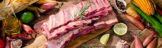 Raw beef ribs and vegetables on  dark wooden background. Stock Photos