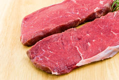 Raw beef-roast beef meat steak on the wooden backg Stock Photography