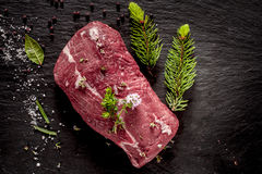 Raw Beef Roast Seasoned with Fresh Herbs. High Angle View of Raw Beef Roast Seasoned with Fresh Herbs and Spices on Dark Grey Textured Surface stock photography