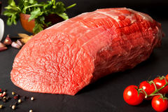 Raw beef round. Still life raw beef round over black ground Stock Images