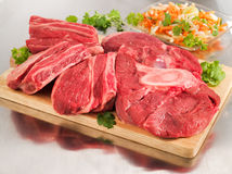 Raw beef shank on cutting board. Raw beef shank steak on cutting board and steel table Royalty Free Stock Image