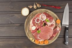 Raw beef shin and vegetables. Sales of beef. Preparing meat for cooking. Raw meat on a cutting board ready for cutting. Royalty Free Stock Images