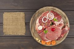 Raw beef shin and vegetables. Sales of beef. Preparing meat for cooking. Raw meat on a cutting board ready for cutting. Royalty Free Stock Photography