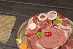 Raw beef shin and vegetables. Sales of beef. Preparing meat for cooking. Raw meat on a cutting board ready for cutting. Royalty Free Stock Photos