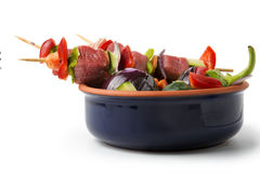 Raw beef skewers in a blue bowl, isolated background. Raw beef skewers in a blue bowl, with fresh vegetables on isolated background Stock Photography