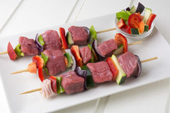Raw beef skewers. With fresh vegetables on rectangular plate and white wooden table Stock Photography