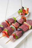 Raw beef skewers. With fresh vegetables on rectangular plate and white wooden table Royalty Free Stock Photos
