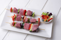 Raw beef skewers. With fresh vegetables on rectangular plate and white wooden table Royalty Free Stock Image