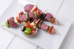 Raw beef skewers. With fresh vegetables on rectangular plate and white wooden table Stock Photo