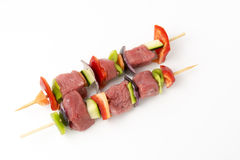 Raw beef skewers, isolated background. Raw beef skewers, with fresh vegetables and white background Stock Image