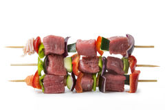 Raw beef skewers, isolated background. Raw beef skewers, with fresh vegetables and white background Stock Photo