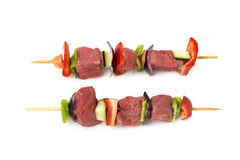 Raw beef skewers, isolated background. Raw beef skewers, with fresh vegetables and white background Royalty Free Stock Photo