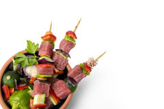 Raw beef skewers, isolated background. Raw beef skewers, with fresh vegetables and white background Stock Images