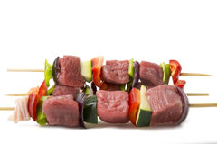 Raw beef skewers, isolated background. Raw beef skewers, with fresh vegetables and white background Royalty Free Stock Image