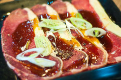 Raw beef sliced. Fresh raw beef sliced with sauce and vegetable on black plate Stock Images