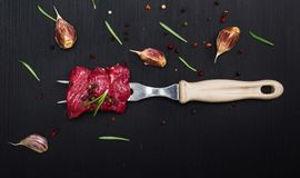 Raw beef slices are strung on a kitchen fork. Sprinkled with spices, top view Royalty Free Stock Image