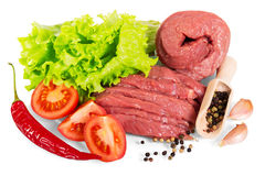 Raw beef with spices, lettuce and tomatoes isolated on white. Raw beef with spices, lettuce and tomatoes isolated on white background Stock Photo