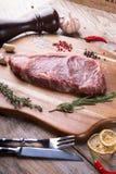 Raw beef sreak. On a wooden board Royalty Free Stock Photos
