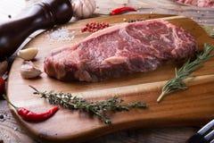 Raw beef sreak. On a wooden board Royalty Free Stock Image