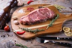 Raw beef sreak. On a wooden board Stock Image