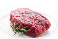 Raw beef steak. Fresh raw beef steak on white plate close up Stock Images